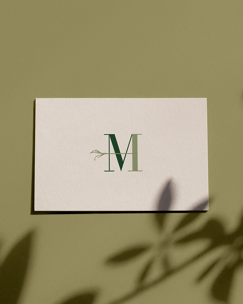 Mahan Health business card on a green backdrop with shadows from a plant