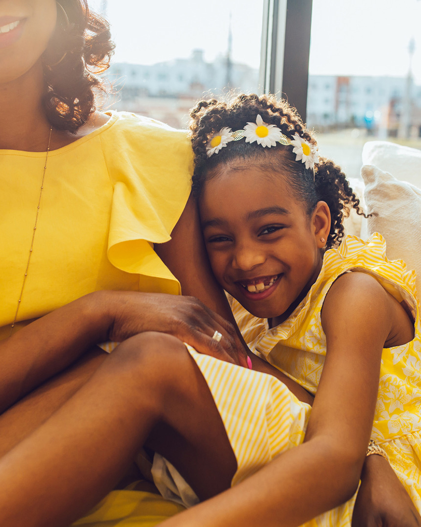 Penzone Salons photo of a young Black girl in a bright yellow dress laughing with a Black woman